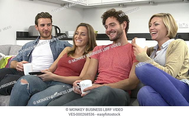 Group of friends sitting on sofa and watching TV together.Shot on Sony FS700 in PAL format at a frame rate of 25fps