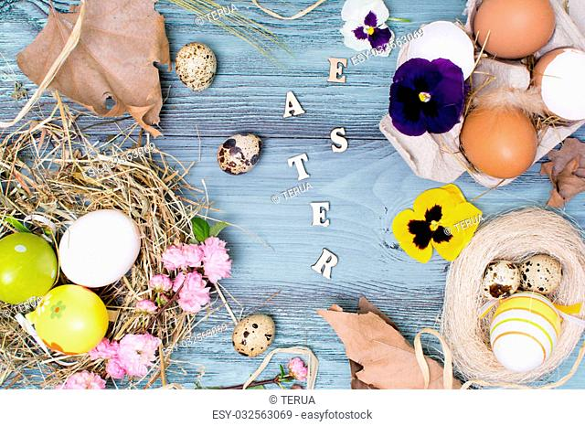 Easter background with eggs and flowers. Different egg types with flowers on the wooden background. Top view