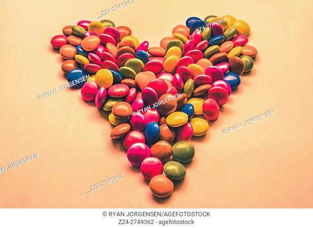 Cute still life kitchen artwork on a gathering of chocolate coated candy balls mixed together to symbolise love and hearts