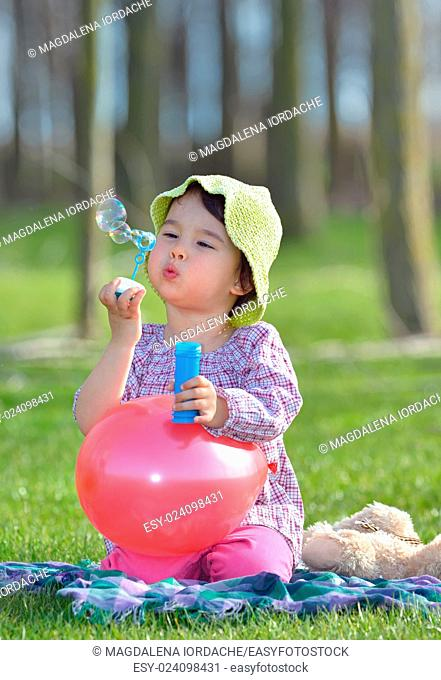 little girl is blowing a soap bubbles in forest