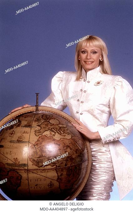 Raffaella Carrà near a globe. Italian TV presenter, actress, singer and showgirl Raffella Carrà (Raffaella Maria Roberta Pelloni) leaning on a globe