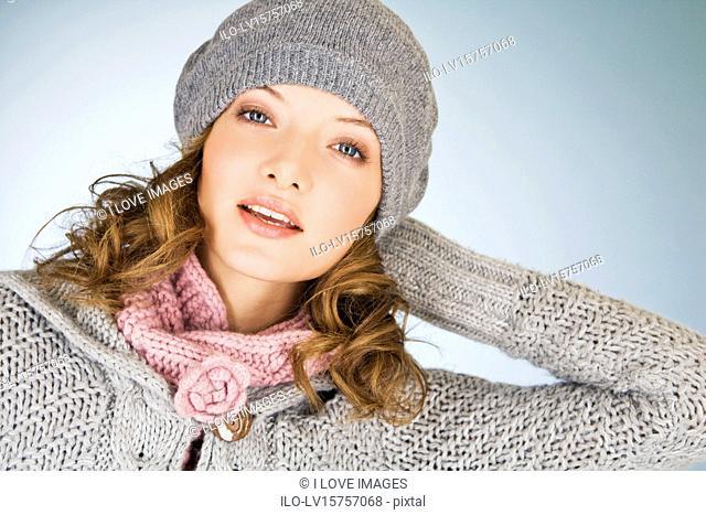 Portrait of a young woman wearing a grey woollen hat