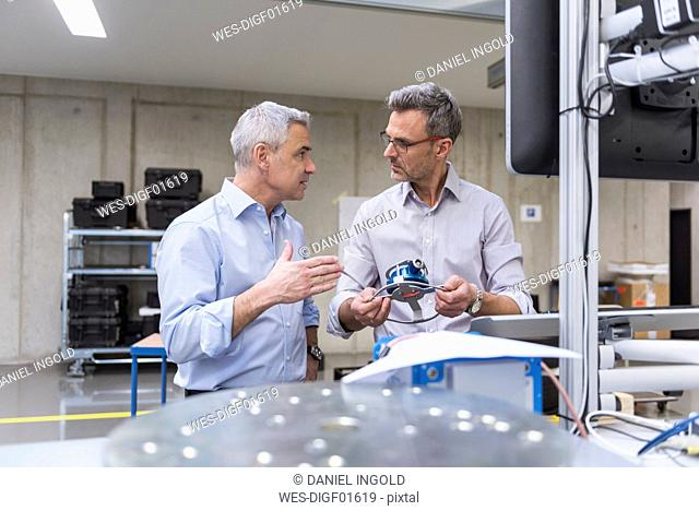 Two businessmen in factory hall examining product