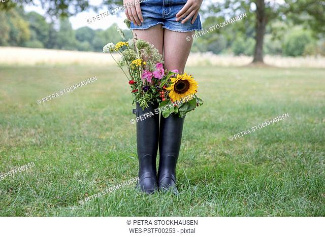 Legs of girl standing on a meadow with bunches of flowers in her rubber boots