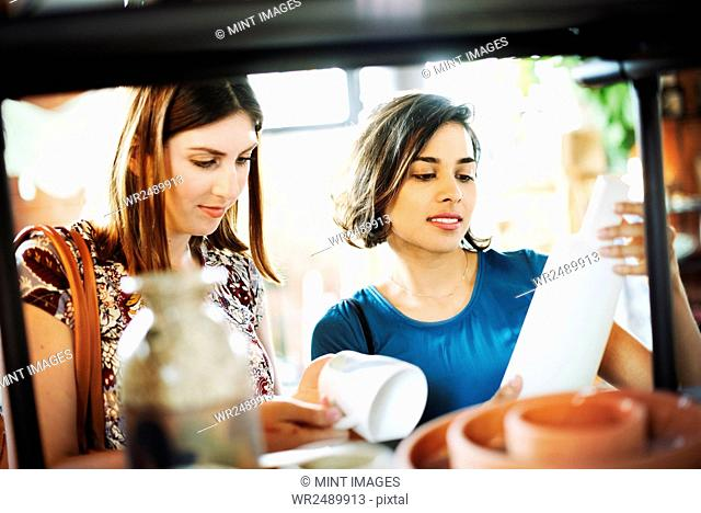 Two young women in a shop, looking at a white ceramic vase and mug