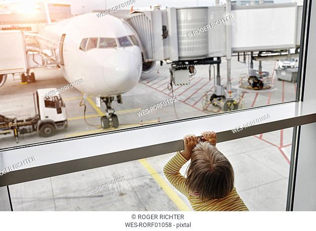Little girl looking through window to airplane on the apron