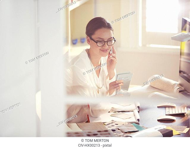 Interior designer examining fabric swatches and talking on cell phone in office