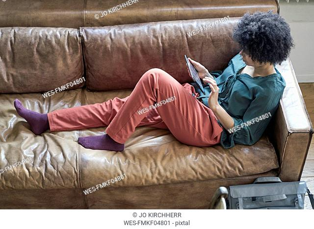 Young woman lying on couch using tablet