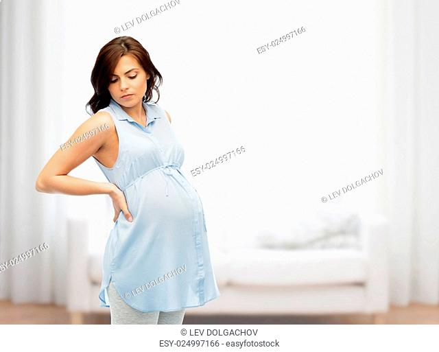 pregnancy, health, people and expectation concept - pregnant woman touching her back and suffering from backache over home living room background