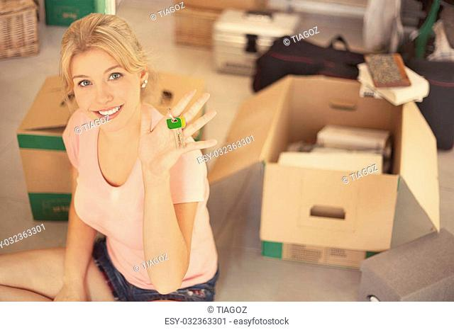 Blond young woman holding key of new house