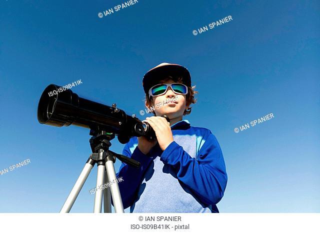 Boy with telescope on tripod