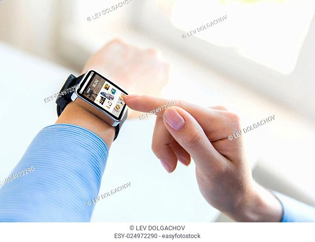 business, modern technology, blogging, media and people concept - close up of female hands setting smart watch with internet blog on screen at office