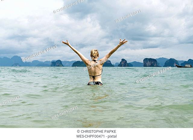 Thailand, Koh Yao Noi, back view of happy woman standing in the sea