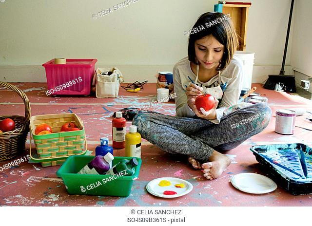 Girl sitting cross-legged painting fruit