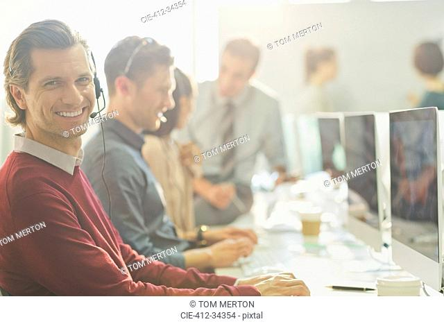 Portrait smiling telemarketer talking on telephone with headset at computer