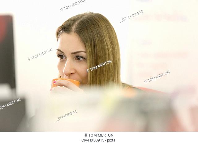 Businesswoman sipping coffee at computer