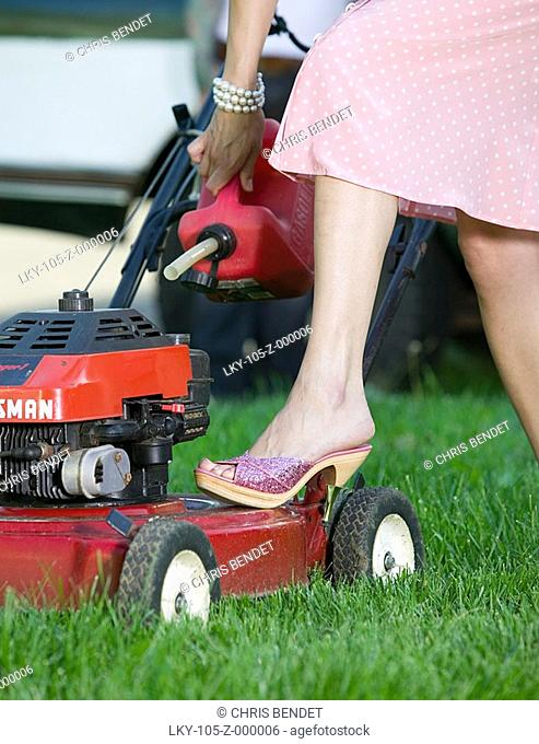 Woman in dress and heels pouring gas in lawnmower