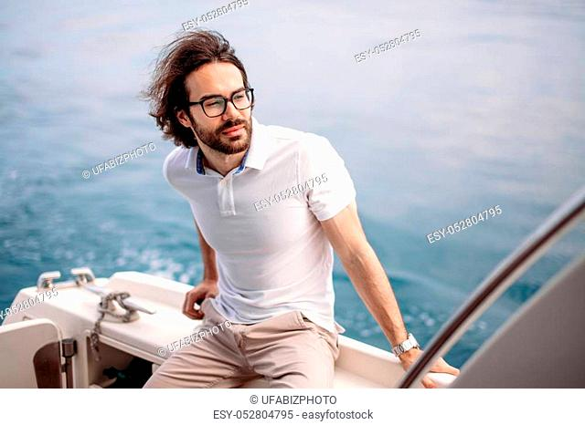 Portrait of adult caucasian bearded tourist taking not far-avay sea journey on luxury white yacht in Caribbean sea