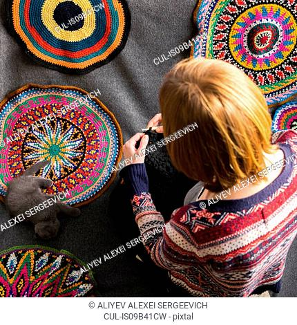 Overhead view of woman sitting on floor crocheting, surrounded by crochet circles