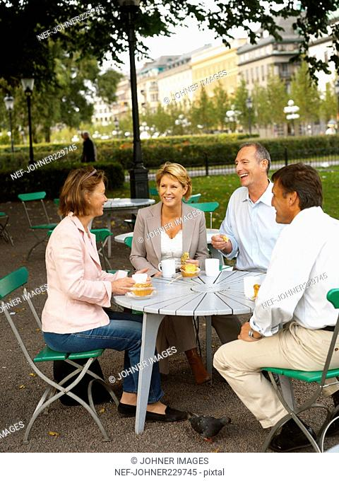 Four people having coffee outdoors