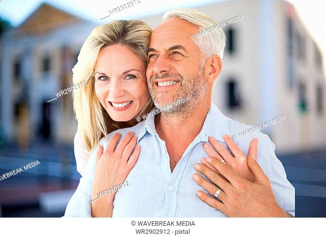 Happy woman embracing man against house