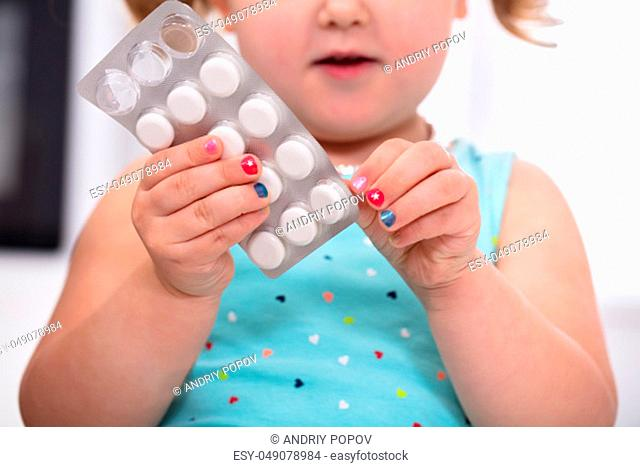 Close-up Of Girls Hand Removing Tablet From Blister Pack
