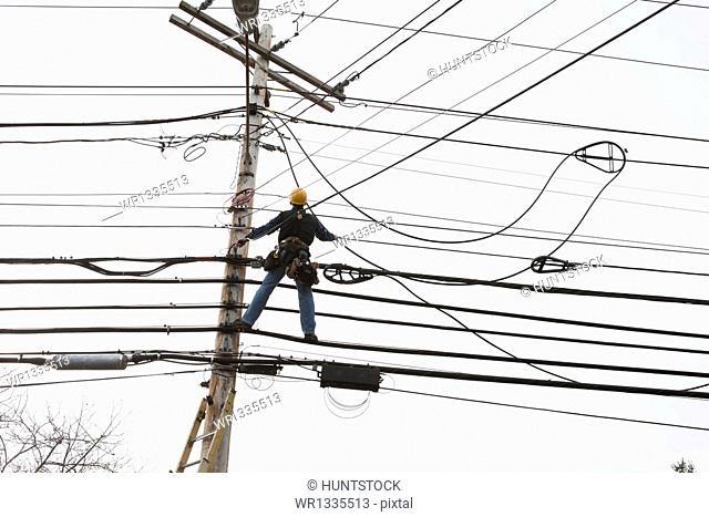 Communications worker on a power pole installing new cable to existing bundles