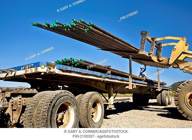 Loading drill pipe in oil-gas well area in Colorado