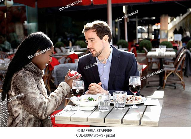 Couple enjoying meal at cafe, woman opening red box, smiling, looking surprised
