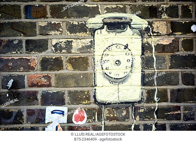 Graffitti image of an old phone, drawn on a brick wall in East End, London, England, UK, Europe