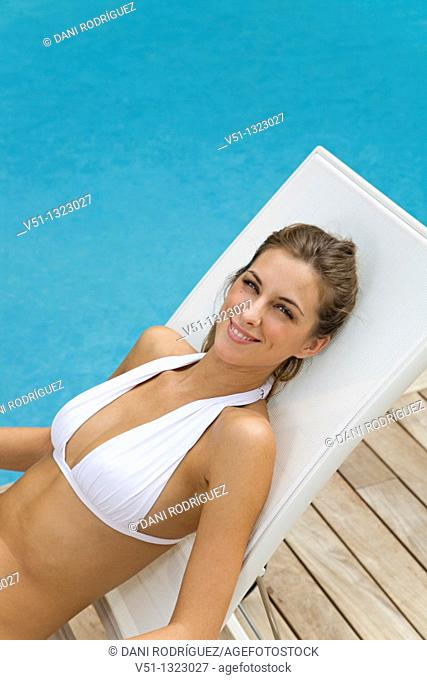 Young woman enjoying sun in hammock by the pool