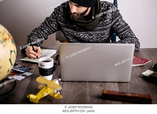 Man with map and laptop planning a trip