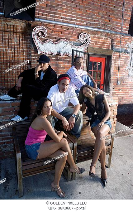 Portrait of young men and women in hip-hop fashion hanging out in a back alley