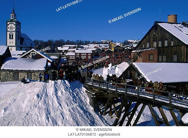 Winter. Town,houses. Market. Large crowd of people. Watching people in sleighs pulled by ponies