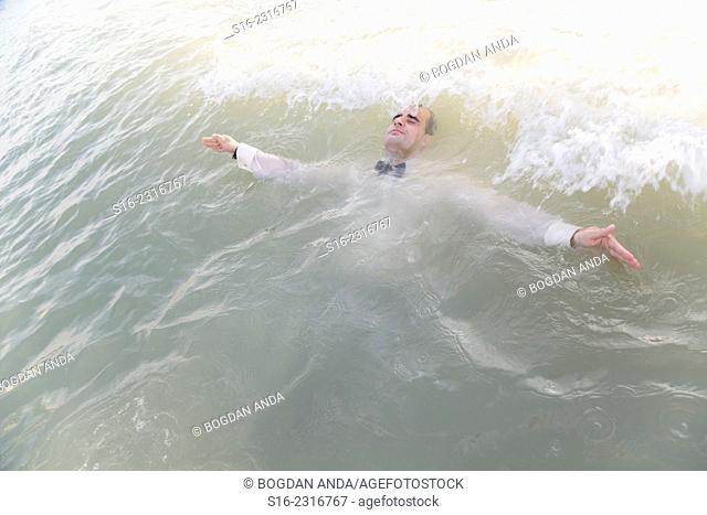 Dressed up young man surrendering to sea waves
