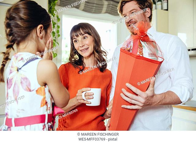 Parents presenting school cone to their daughter