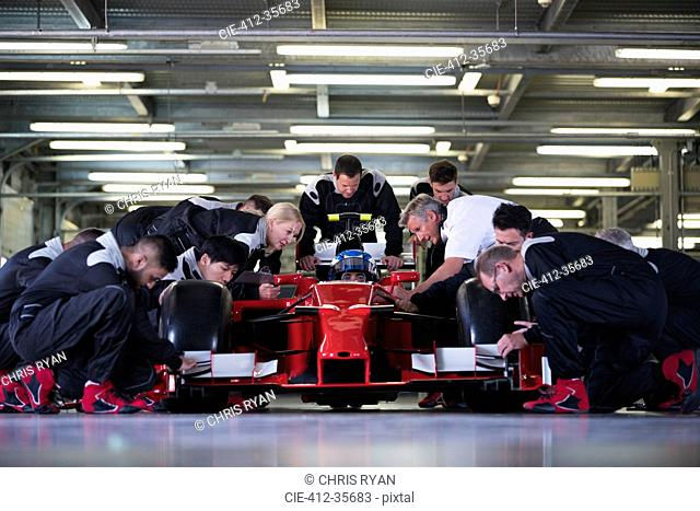 Pit crew preparing formula one race car and driver in repair garage