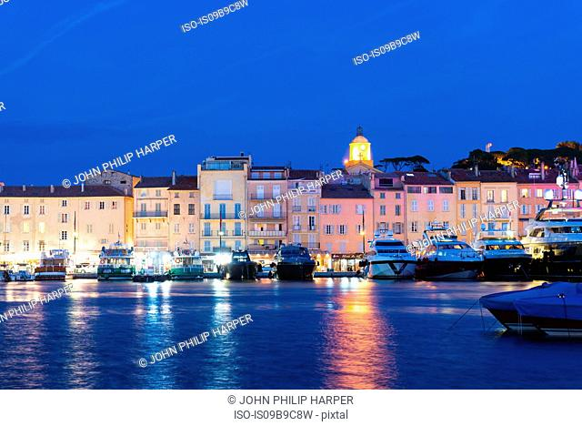 Superyachts and townhouses on waterfront at night, St Tropez, Cote d'Azur, France
