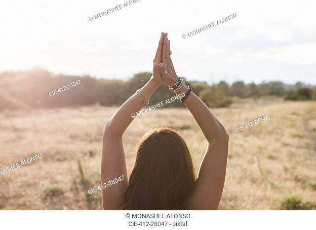 Woman meditating with hands clasped overhead in sunny rural field