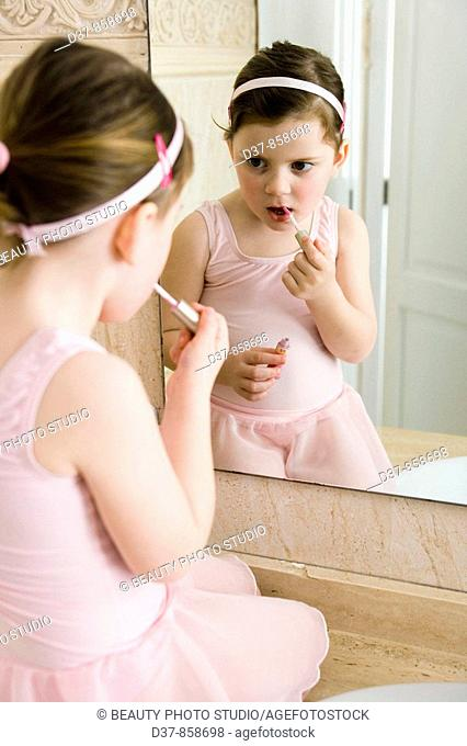 Little girl applying make up