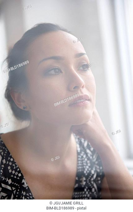 Tranquil woman looking out window