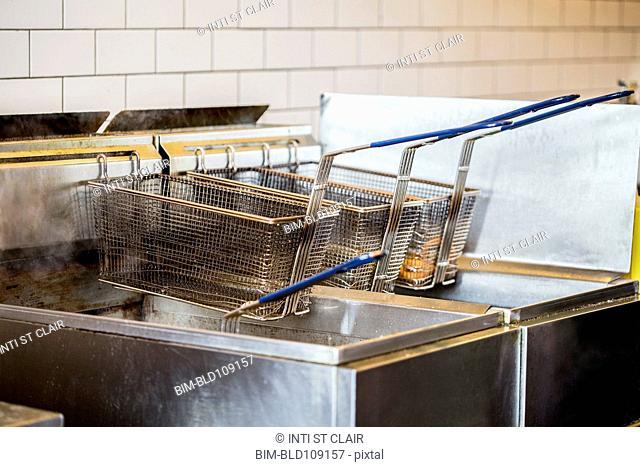 Baskets on deep fat fryer in restaurant