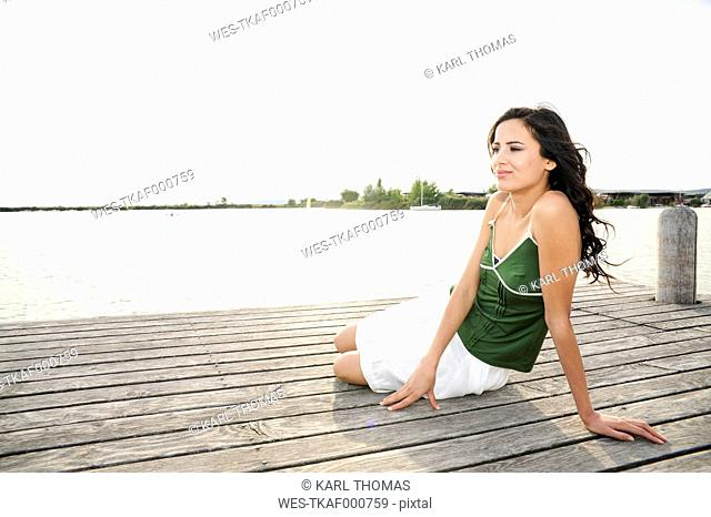 Austria, Jois, young woman relaxing on jetty at Lake Neusiedl