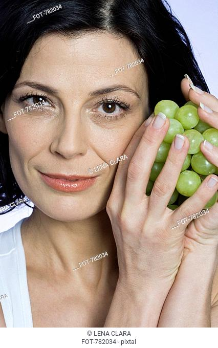 A woman holding a bunch of grapes