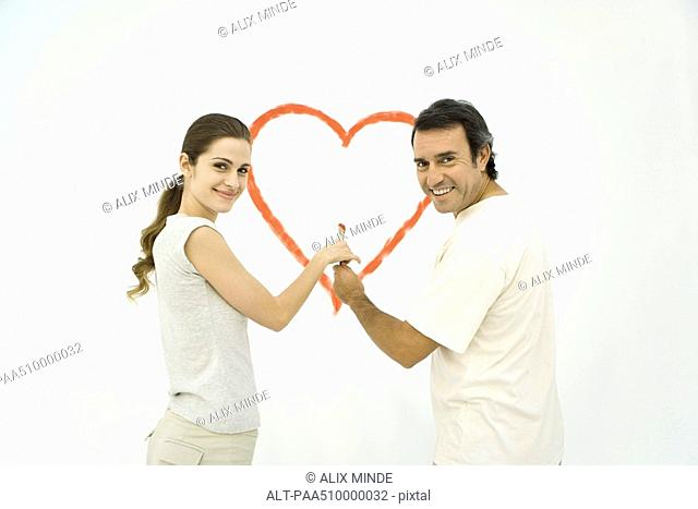Couple standing in front of heart painted on wall, both holding onto the same paintbrush