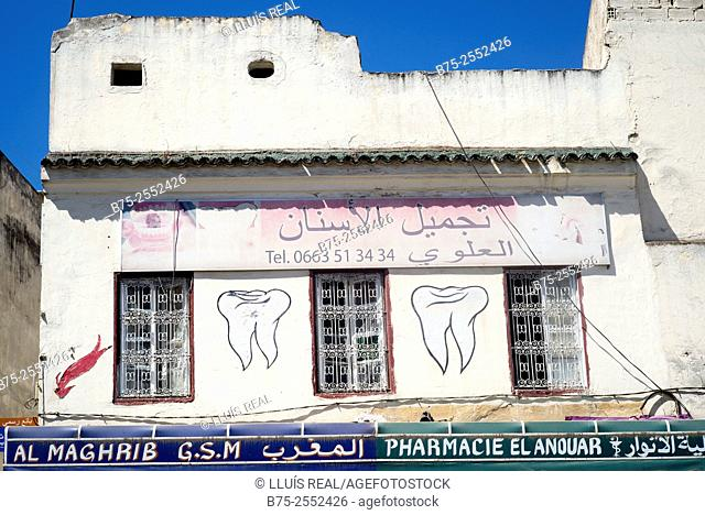 Facade with hand-drawn advertisement of a dentist and a pharmacy in the medina. Fez, Morocco, Africa