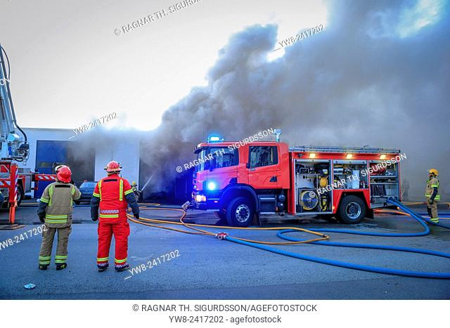 Firemen at the scene of a fire involving a small buisness. Kopavogur, Iceland