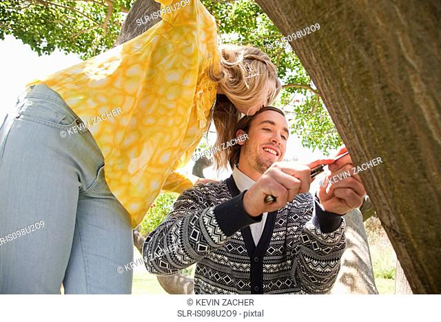 Young couple carving names on a tree