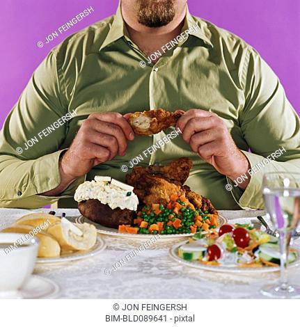 Overweight man eating fried chicken dinner
