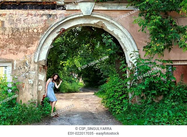 Girl in beautiful pose in dress stands near arch